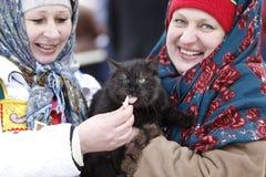 Οι ρωσικές γυναίκες στα μαντίλι για το κεφάλι ταΐζουν τη γάτα Εθνικό ρωσικό φεστιβάλ Masl Στοκ Φωτογραφίες