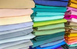 Οι ρόλοι του υφάσματος και των κλωστοϋφαντουργικών προϊόντων σε ένα εργοστάσιο ψωνίζουν ή αποθηκεύουν ή bazar απεικόνιση αποθεμάτων