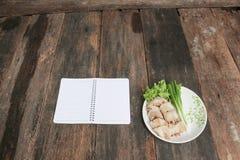 Οι ρόλοι άνοιξη χύνουν τη σάλτσα στενό σε επάνω πιάτων με το σημειωματάριο και το φρέσκο λαχανικό σε ξύλινο Στοκ Εικόνα