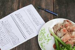 Οι ρόλοι άνοιξη χύνουν τη σάλτσα στενό σε επάνω πιάτων με το σημειωματάριο και το φρέσκο λαχανικό σε ξύλινο Στοκ Εικόνες