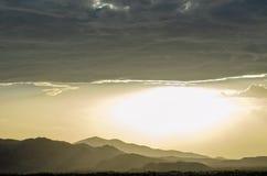 Οι σειρές βουνών κάτω από την παχιά τράπεζα της βροχής καλύπτουν και φωτεινός μουντός ουρανός στη έρημο Μοχάβε στοκ φωτογραφία