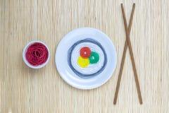 Οι σειρές στα διαφορετικά χρώματα με μορφή σουσιών κυλούν και σάλτσας σόγιας με τα ραβδιά στην μπεζ minimalistic αφηρημένη έννοια Στοκ Φωτογραφίες