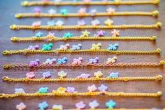 Οι σειρές της χρυσής αλυσίδας βραχιολιών με τα χαριτωμένα κρεμαστά κοσμήματα για την πώληση στο κόσμημα ψωνίζουν Χρυσές χειροποίη Στοκ Φωτογραφία
