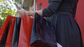 Οι σε απευθείας σύνδεση αγορές, κορίτσι αγοραστών χρησιμοποιούν το κινητό τηλέφωνο για την αγορά και την πληρωμή σε Διαδίκτυο στη φιλμ μικρού μήκους