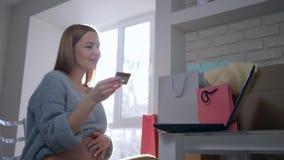 Οι σε απευθείας σύνδεση αγορές, νέο θηλυκό μητρότητας με την πλαστική κάρτα χρησιμοποιούν το φορητό προσωπικό υπολογιστή για την  απόθεμα βίντεο