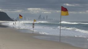Οι σημαίες που δείχνουν τις φρουρές ζωής κυματωγών είναι στην περίπολο, ξημερώματα Palm Beach, Queensland Αυστραλία φιλμ μικρού μήκους