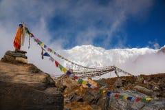 Οι σημαίες προσευχής και το βουνό χιονιού κυμαίνονται το υπόβαθρο από το στρατόπεδο βάσεων Annapurna, Νεπάλ Στοκ Φωτογραφία