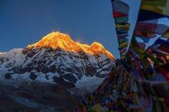 Οι σημαίες προσευχής και το βουνό Annapurna κυμαίνονται το υπόβαθρο από το στρατόπεδο βάσεων Annapurna, Νεπάλ Στοκ φωτογραφία με δικαίωμα ελεύθερης χρήσης