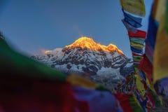 Οι σημαίες προσευχής και το βουνό Annapurna κυμαίνονται το υπόβαθρο από το στρατόπεδο βάσεων Annapurna, Νεπάλ Στοκ Εικόνες