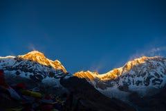 Οι σημαίες προσευχής και το βουνό Annapurna κυμαίνονται το υπόβαθρο από το στρατόπεδο βάσεων Annapurna, Νεπάλ Στοκ Φωτογραφία