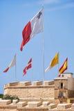 Οι σημαίες χτυπούν πέρα από τους τοίχους φρουρίων για διακοπές Μάλτα Στοκ Εικόνα
