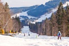 Οι σκιέρ και snowboarder κατεβαίνουν από το βουνό Στοκ Φωτογραφία