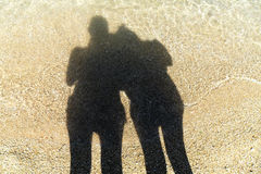 Οι σκιές, περιγράφουν τη σκιαγραφία στην ηλιόλουστη άμμο στη ρηχή θάλασσα Στοκ φωτογραφία με δικαίωμα ελεύθερης χρήσης