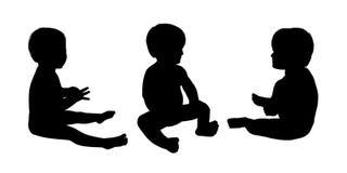 Οι σκιαγραφίες λίγης συνεδρίασης μωρών θέτουν 2 Στοκ φωτογραφία με δικαίωμα ελεύθερης χρήσης