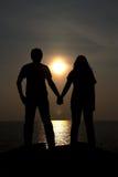 Οι σκιαγραφίες απεικονίζουν την αγάπη των ζευγών με το όμορφο σκηνικό ηλιοβασιλέματος Στοκ Φωτογραφία