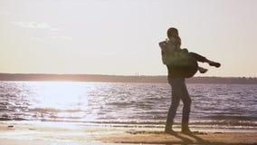 Οι σκιαγραφίες κοριτσιών ` s με τον τύπο στη θάλασσα Ένα ηλιοβασίλεμα στην παραλία Νέος περίπατος ζευγών στην ακτή φιλμ μικρού μήκους