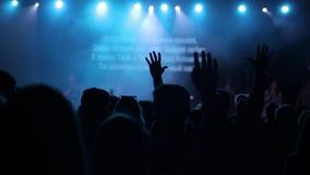 Οι σκιαγραφίες των νέων με ανυψωμένος επάνω δίνουν το τραγούδι και το χορό σε μια συναυλία απομονωμένο οπισθοσκόπο λευκό απόθεμα βίντεο