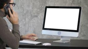 Οι σοβαρές συγκεντρωμένες αρσενικές κλήσεις εργαζομένων γραφείων με το τηλέφωνό του και λειτουργούν στον υπολογιστή Άσπρη παρουσί απόθεμα βίντεο