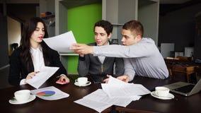Οι σοβαροί εργαζόμενοι και επιχειρηματίες, δύο τύποι και το κορίτσι συζητούν περίπου Στοκ εικόνα με δικαίωμα ελεύθερης χρήσης