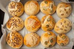 Οι σπιτικοί ρόλοι ψωμιού με το χάμπουργκερ σπόρων σουσαμιού με το σουσάμι, κολοκύθα, λινάρι, σπόροι ηλίανθων στο δίσκο, έννοια bu στοκ φωτογραφία