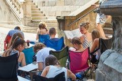 Οι σπουδαστές αρχιτεκτονικής που σύρουν τις αρχιτεκτονικές λεπτομέρειες κατά τη διάρκεια του En plein αερίζουν την ανάθεση κοντά  Στοκ Εικόνες