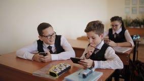 Οι σπουδαστές γυμνασίου παίζουν τα παιχνίδια στο τηλέφωνό τους κατά τη διάρκεια της κατηγορίας απόθεμα βίντεο