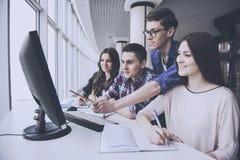 Οι σπουδαστές εξετάζουν στον υπολογιστή το πανεπιστήμιο στοκ εικόνες
