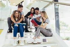 Οι σπουδαστές μελετούν στη βιβλιοθήκη Οι νέοι ξοδεύουν το χρόνο από κοινού Βιβλίο ανάγνωσης και επικοινωνία ενώ στοκ φωτογραφία