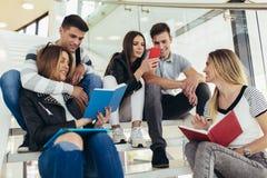 Οι σπουδαστές μελετούν στη βιβλιοθήκη Οι νέοι ξοδεύουν το χρόνο από κοινού Βιβλίο ανάγνωσης και επικοινωνία ενώ στοκ φωτογραφίες με δικαίωμα ελεύθερης χρήσης