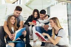 Οι σπουδαστές μελετούν στη βιβλιοθήκη Οι νέοι ξοδεύουν το χρόνο από κοινού Βιβλίο ανάγνωσης και επικοινωνία ενώ στοκ φωτογραφία με δικαίωμα ελεύθερης χρήσης