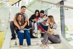 Οι σπουδαστές μελετούν στη βιβλιοθήκη Οι νέοι ξοδεύουν το χρόνο από κοινού Βιβλίο ανάγνωσης και επικοινωνία ενώ στοκ εικόνες με δικαίωμα ελεύθερης χρήσης