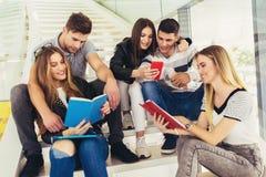 Οι σπουδαστές μελετούν στη βιβλιοθήκη Οι νέοι ξοδεύουν το χρόνο από κοινού Βιβλίο ανάγνωσης και επικοινωνία ενώ στοκ εικόνα