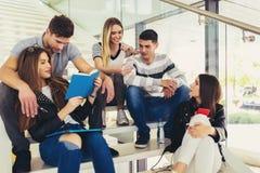 Οι σπουδαστές μελετούν στη βιβλιοθήκη Οι νέοι ξοδεύουν το χρόνο από κοινού Βιβλίο ανάγνωσης και επικοινωνία ενώ στοκ εικόνες