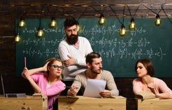 Οι σπουδαστές, ομάδα ζευγαρώνουν την ομιλία, τη ζήτηση τις συμβουλές ή την εξαπάτηση ενώ δάσκαλος που προσέχει τους Γενειοφόρος δ Στοκ Εικόνα