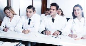 Οι σπουδαστές στα άσπρα παλτά ακούνε για να μιλήσουν Στοκ Φωτογραφία