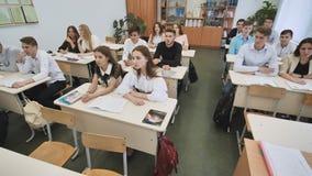 Οι σπουδαστές στην τάξη εξετάζουν τον πίνακα κατά τη διάρκεια του μαθήματος στοκ φωτογραφία
