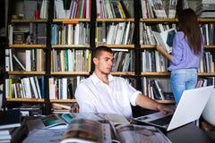 Οι σπουδαστές επικοινωνούν σε μια βιβλιοθήκη νεαρός άνδρας και γυναίκα που μιλούν στη βιβλιοθήκη Στοκ Φωτογραφίες