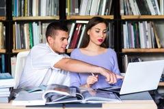 Οι σπουδαστές επικοινωνούν σε μια βιβλιοθήκη νεαρός άνδρας και γυναίκα που μιλούν στη βιβλιοθήκη Στοκ φωτογραφία με δικαίωμα ελεύθερης χρήσης