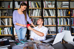 Οι σπουδαστές επικοινωνούν σε μια βιβλιοθήκη νεαρός άνδρας και γυναίκα που μιλούν στη βιβλιοθήκη Στοκ Φωτογραφία