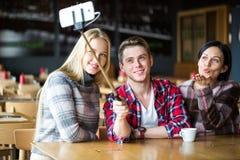 Οι σπουδαστές κάνουν selfie σε έναν καφέ Αγόρι και δύο κορίτσια κάνουν selfie στον καφέ Στοκ εικόνες με δικαίωμα ελεύθερης χρήσης