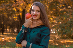 Οι στάσεις νέων κοριτσιών στο πάρκο κρατούν τη Apple στο χέρι και την κινηματογράφηση σε πρώτο πλάνο χαμόγελού του Στοκ Εικόνες