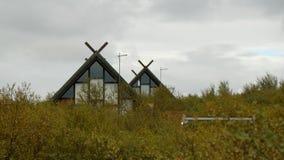 Οι στέγες δύο σπιτιών, που μοιάζουν με τις καλύβες, κοιτάζουν έξω από πίσω από τα δέντρα Στοκ Εικόνες