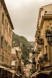 Οι στενές οδοί της πόλης Taormina με τα καταστήματα και τα μεσαιωνικά κτήριά του μια ηλιόλουστη ημέρα Νησί της Σικελίας, Ιταλία Στοκ Φωτογραφία