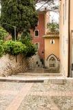 Οι στενές οδοί της πόλης Taormina με τα καταστήματα και τα μεσαιωνικά κτήριά του μια ηλιόλουστη ημέρα Νησί της Σικελίας, Ιταλία Στοκ Εικόνα