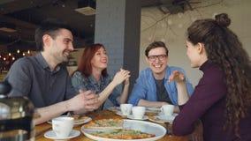 Οι στενοί φίλοι μοιράζονται τις αστείες ιστορίες που και που γελούν ενώ έχοντας το μεσημεριανό γεύμα στο σύγχρονο καφέ θετικό συγ φιλμ μικρού μήκους