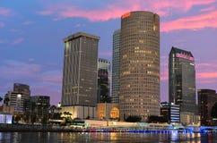 Οι στο κέντρο της πόλης ουρανοξύστες με ζωηρόχρωμο λιμενικός στο όμορφο ηλιοβασίλεμα στοκ φωτογραφίες