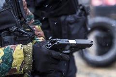 Οι στρατιώτες εκπαιδεύουν το πυροβολισμό με ένα πυροβόλο όπλο μια ομάδα στρατιωτών ασκεί στον κρύο χιονώδη καιρό Στοκ Φωτογραφία