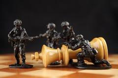 Οι στρατιώτες παιχνιδιών σκοτώνουν το βασιλιά σκακιού Στοκ Εικόνες