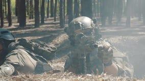 Οι στρατιώτες παλεύουν σε μια τάφρο σε ένα καπνώές δάσος φιλμ μικρού μήκους