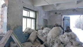 Οι στρατιώτες στην κάλυψη με τα όπλα αγώνα απολύονται στο καταφύγιο του παλαιού κτηρίου, η στρατιωτική έννοια απόθεμα βίντεο